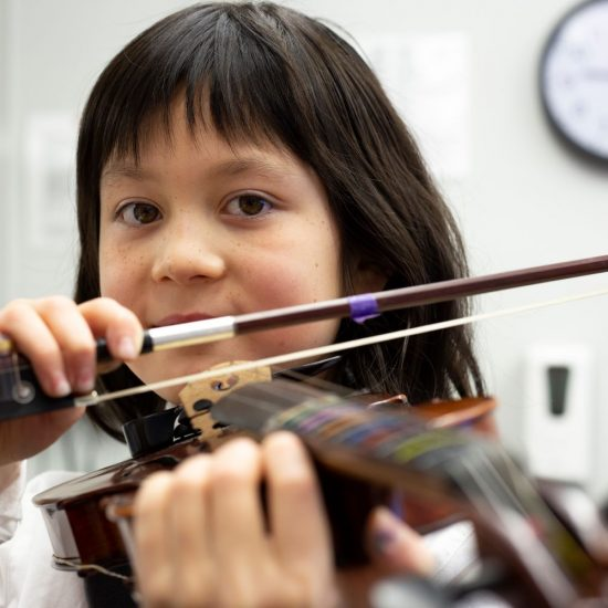 a young school girl playing violin