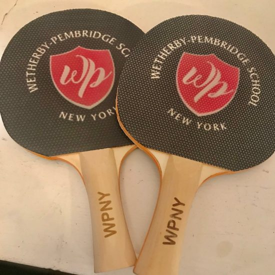 Two Table Tennis Rackets with the logo for Wetherby Pembridge School printed on them