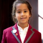 A young girl with brown hair in a Wetherby Pembridge School Uniform, burgundy blazer