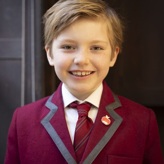 A young boy in a Wetherby Pembridge School uniform, burgundy blazer and tie