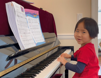 A young child in a red t-shirt learning to play the piano.