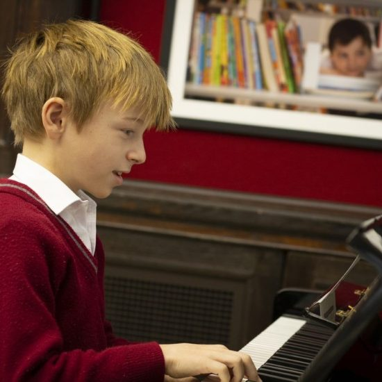 A young school boy playing the piano